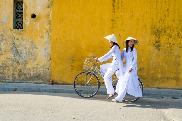 girls in non las riding bike in Vietnam