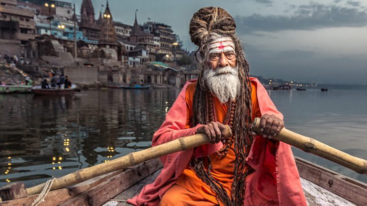 Holy man rowing on the Ganges