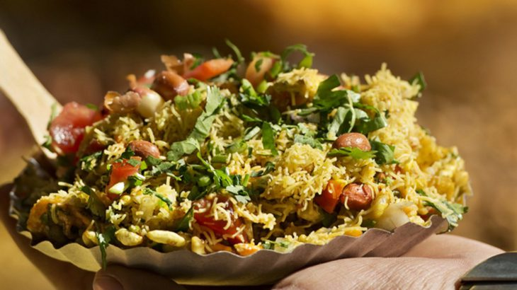 Man holding a plate of Bhelpuri in India