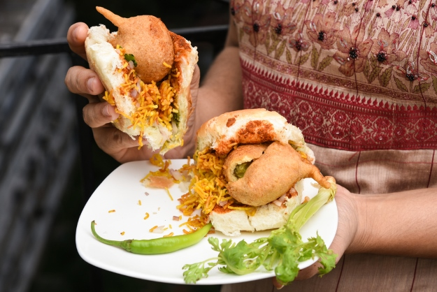Woman eating vegetarian Vada Pav in India