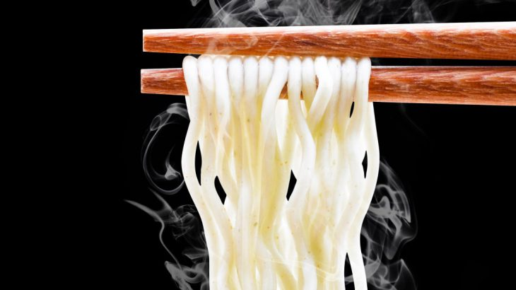 chopsticks with steaming noodles