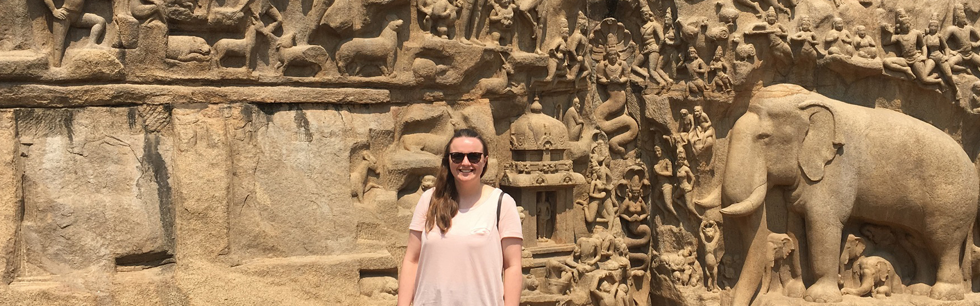 Chloe in front of a wall carving