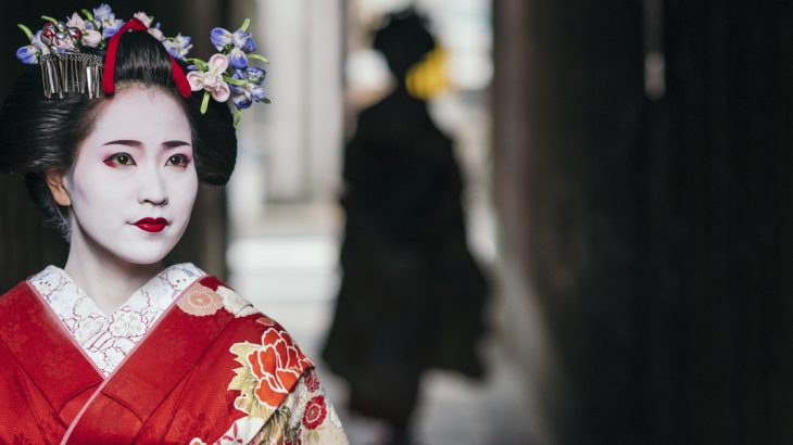 Geisha emerging from an old alleyway