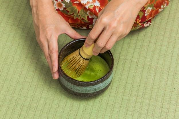 Woman in a kimono whisking matcha tea