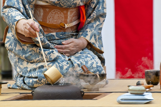 Woman in kimono ladling hot water during a tea ceremony