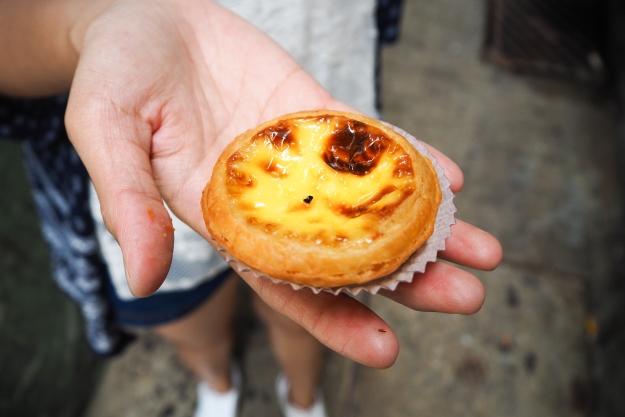 Hand holding an egg tart