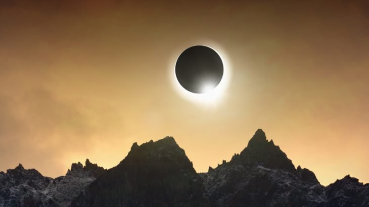 Solar eclipse over jagged mountains