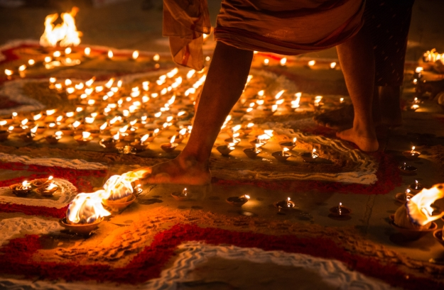 Man walking barefoot amongst candles
