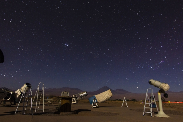 telescopes under a star filled sky