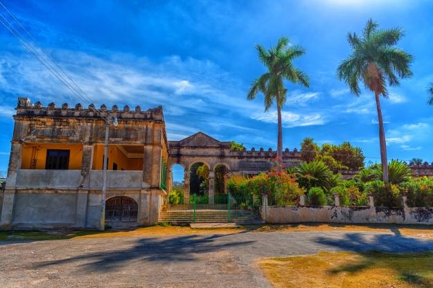 An abandoned hacienda against a blue sky and palm trees