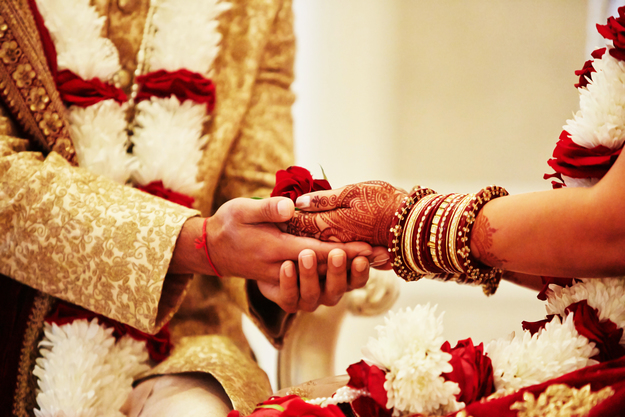 A bride and groom holding hands at an Indian Wedding
