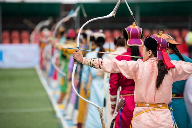 Women in traditional Mongolian dress lined up shooting bows and arrows.